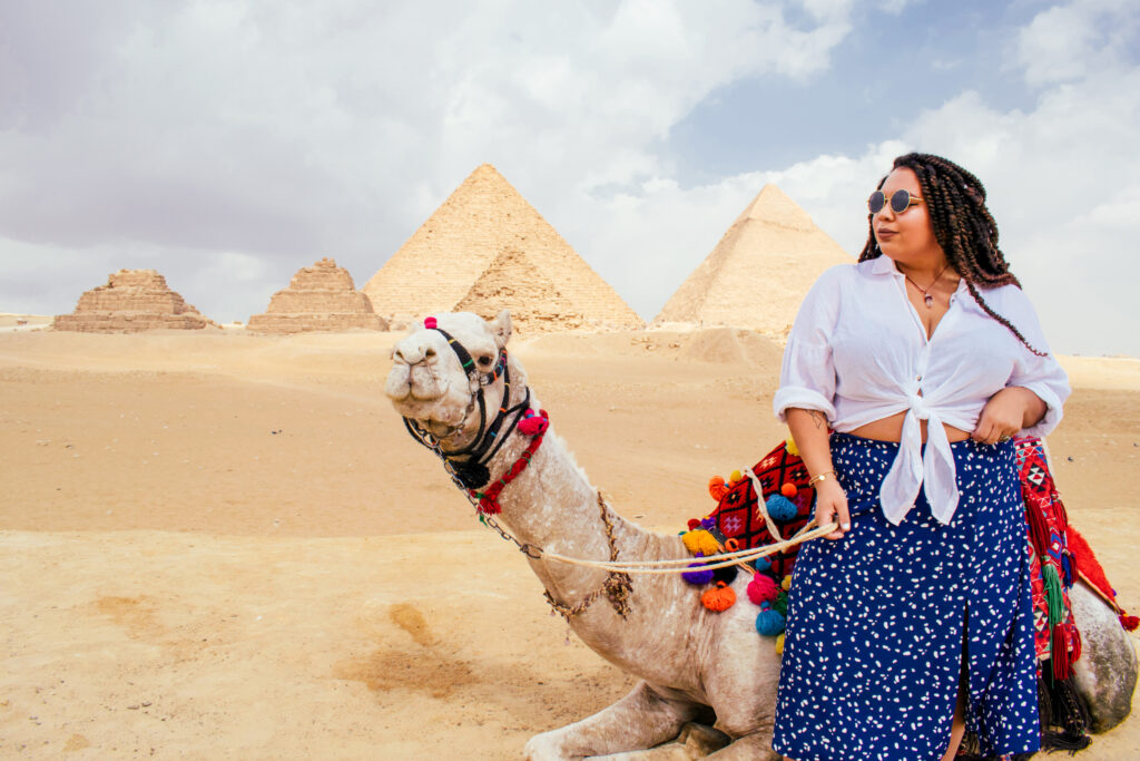 Samantha stands in front of the Great Pyramids in Cairo, Egypt with a camel.